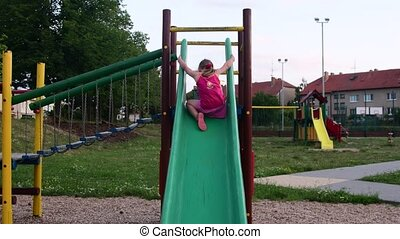 View of girl goes on rope bridge in the playset at playground. Girl on the slide at playground
