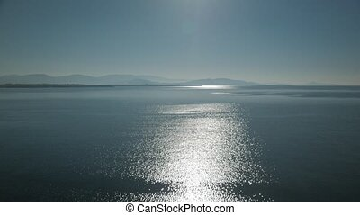 View of glistening and shimmering sea surface with hills on the horizon. Defocused glow of sun reflecting off sea water. 4k.