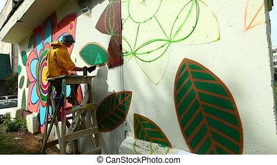 View of graffiti artist working on street
