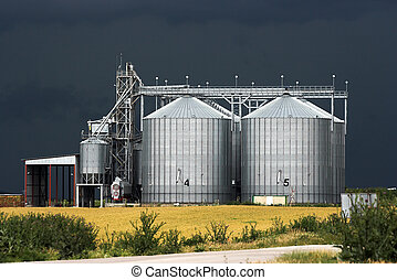 View of grain silos against stormy sky
