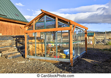 View of green house and chicken coop in a small farm.