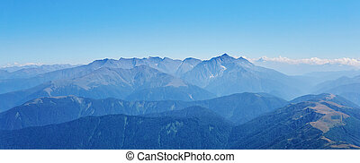 view of high mountains to the horizon from one of the peaks