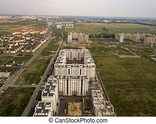 View of high-rise buildings with the playgrounds of neighborhoods in the suburbs overlooking the fields