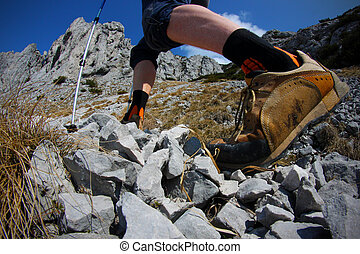 View of hikers legs with trekking boots