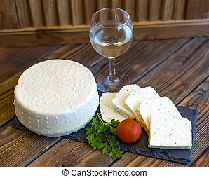 View of homemade cheese head and cheese slicing on a black slate board served with tomatoes, fresh greens and glass of white wine. Shallow depth of field.