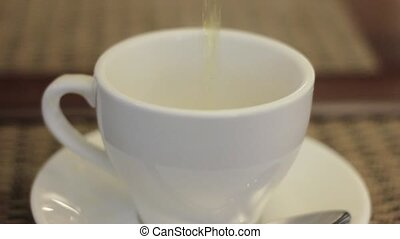 View of hot water pouring into white cup or mug with blurred background