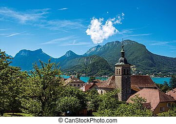 View of houses and belfry with blue sky mountains landscape in Talloires.