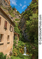 View of houses near creek and bluff with church on top of cliff in the village of Moustiers-Sainte-Marie.