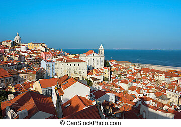 Panoramic view of Alfama toward Igreja de Santo Estevao a church in Lisbon, Portugal and the Tagus river in a bright sunny day.