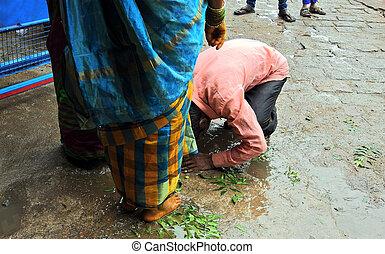 View of Indian Hindu man touching feet of elder woman in offering prayers  and seeking blessings during Bonalu festival