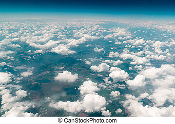 View of  land, fields, and clouds from above