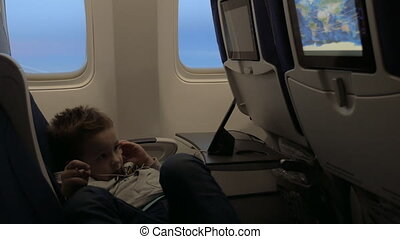 View of little boy watching films in headset in the aircraft lying on the seat against airplane window