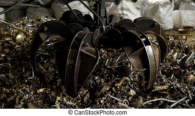 View of metal grabber taking heap of rusty pieces for...