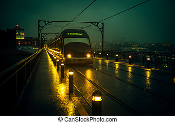 View of metro trains on the Dom Luis I Iron Bridge in cloudy weather at night, Porto, Portugal.
