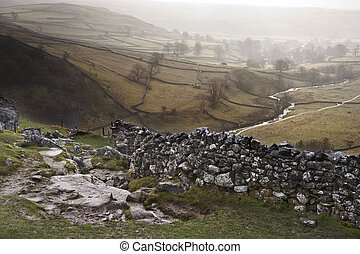 View of misty Malham Dales from limestone pavement above...