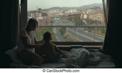 View of mother lying on the bed with small son against huge panoramic window and cityscape, Barcelona, Spain
