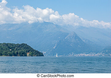 View of mountain lake and the pomontory on a sunny summer day. District of Como Lake, Colico, Italy, Europe