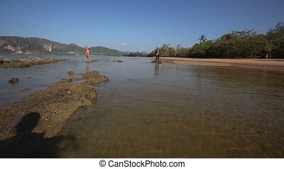 view of moving camera along water towards models under low tide