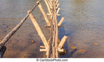 View of Narrow Wooden Bridge with Hand-rails across Water -...