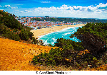 View of Nazare town and the sandy beach seen from high cliff, Portugal