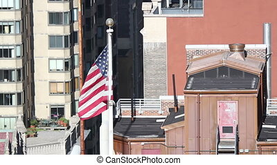view of new york rooftops with an american flag
