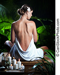 View of nice young woman meditating in spa tropic environment