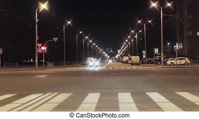 View of night crossroad with traffic lights and cars in city...