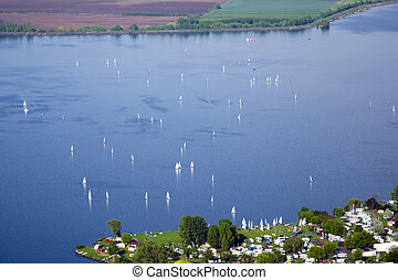 View of Nove Mlyny - Musov lake with boats, sailing boats and windsurfing in the rain in Palava - South Moravia