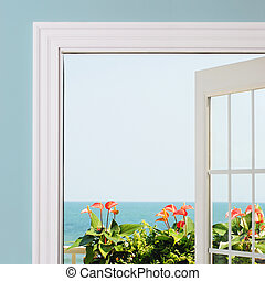 View of ocean from inside of resort / house. Anthurium blooms and green foliage in view.