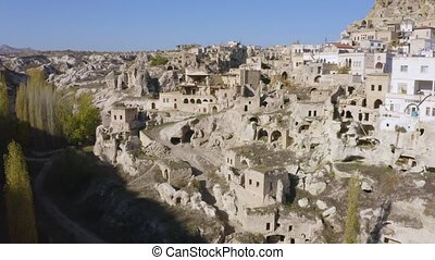 View of Ortahisar town of Cappadocia, Turkey. Natural volcanic rocks with ancient cave houses in Cappadocia, Turkey.
