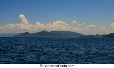 view of passing by boat against clouds sky mountains