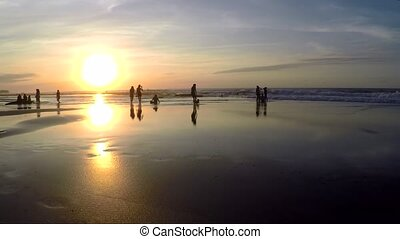 View of people relaxing on beach during sunset