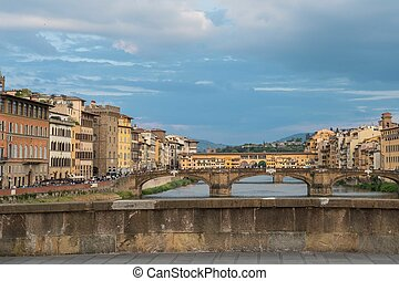 View of Ponte Santa Trinita or St Trinity Bridge and Ponte Vecchio, Bridge over Arno river in Florence, Italy over the sunset.