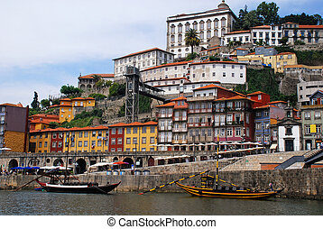 """View of Porto city at the riverbank (Ribeira quarter) and wine boats(""""Rabelo"""") on River Douro(Portugal), a UNESCO World Heritage City."""