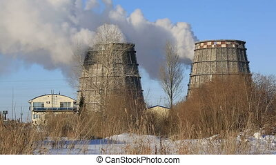 View of power heat station, smoke from the chimney on frosty winter day