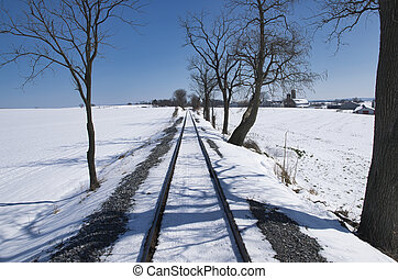Rail Road Tracks Running Thru the Countryside Covered in Snow