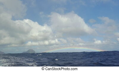 View of rainbow against blue sky with clouds in Indian Ocean, Mauritius Island