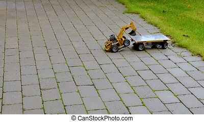 View of R/C model excavator and trailer on background. Free time Children and adults concept.