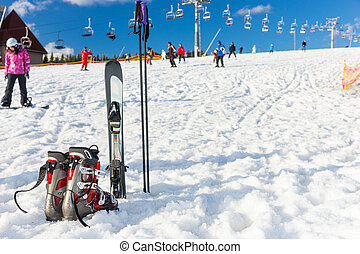 View of red and gray boots next to ski laying in fluffy snow in a ski-resort