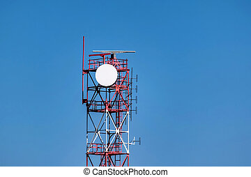 View of red and white communication tower against blue sky