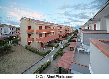 view of resort on coast. orange-storey villas with private balconies