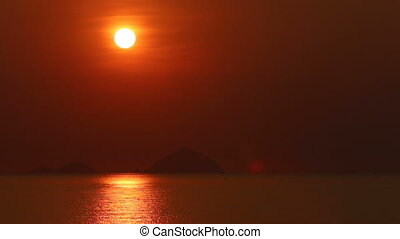 view of rising sun above sea against islands