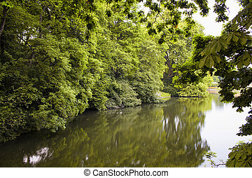 View of river and trees at Hofgarten park. Lush green space with meadows & formal flowerbeds, plus a pond, bandstand.
