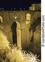 View of Ronda old stone bridge at night, Malaga, Spain