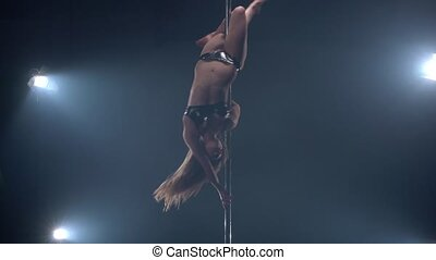 View of sexy girl dancing upside down on pylon - View of...