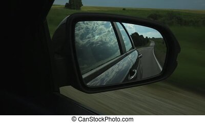 View of side mirror in a car, reflection of clouds and countryroad through the countryside on a summer day