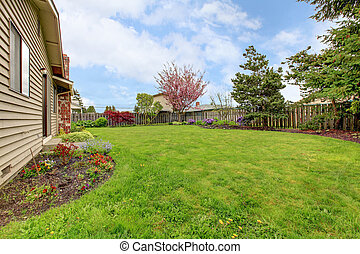 Fenced backyard with green lawn and flower beds