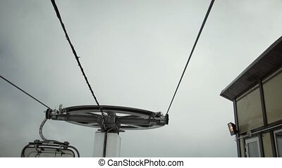 View of ski lifts construction at mountains. Ski resort. Snowboarding. Open cabin. Clouds. Height
