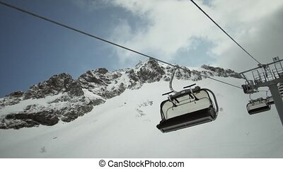 View of ski lifts ride down without people at snowy mountains. Ski resort. Snowboarding. Open cabin