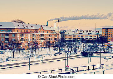View of small swedish european town Soderhamn at sunrise with smoke from the pipes of plant, industrial enviromental concept